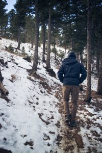Man walking through a snow-dusted forest trail.