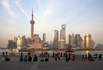 People gaze across the water at the Shanghai skyline.